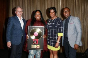 Tasha Cobbs poses with gold award