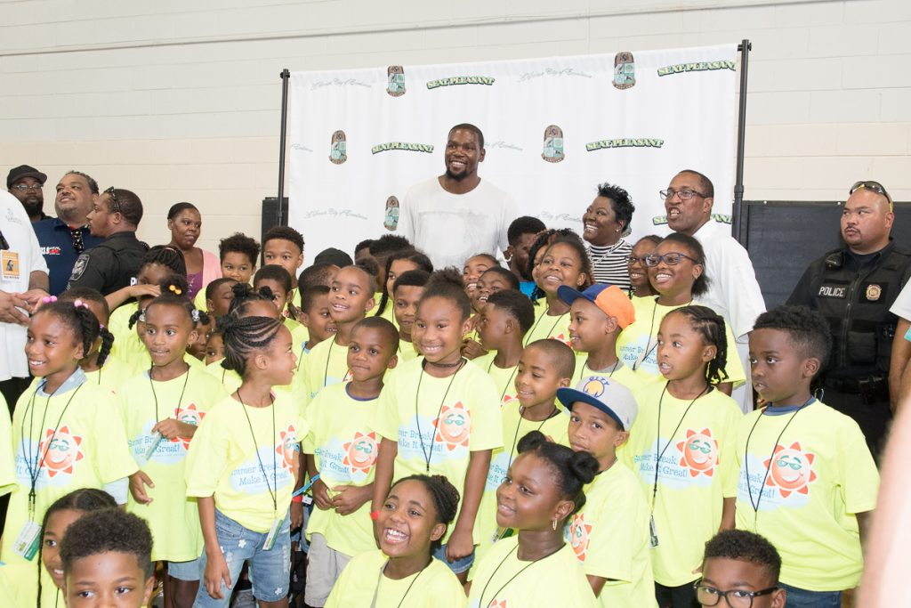 Kevin Durant poses with youth during celebration