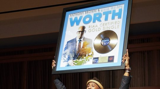 Anthony Brown hoists his god record plaque into the air